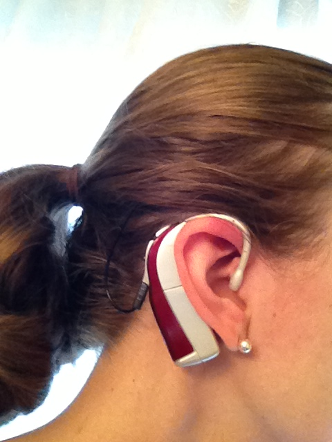 Sveta's burgundy hearing aids complement a Christmas wardrobe.