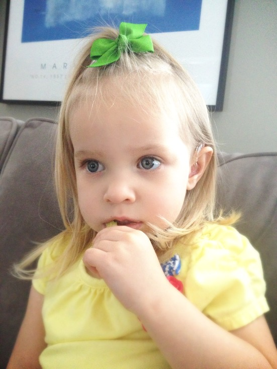 Three-year-old Madeleine was diagnosed with bilateral sensorineural moderate-to-severe hearing loss and has worn hearing aids since the age of six months. Here she is enjoying a snack and her favorite TV show