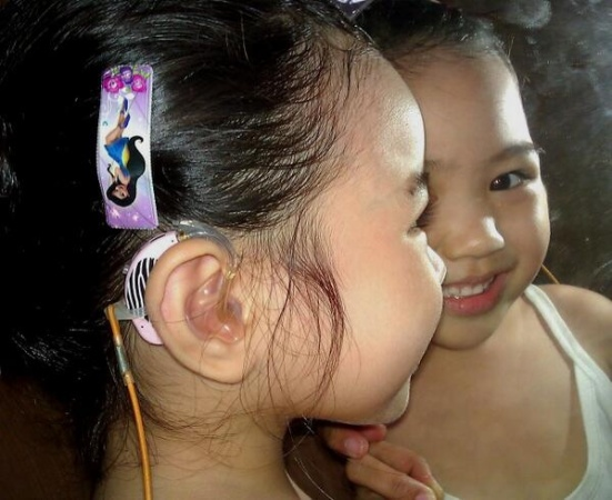 Q, age 3, shows off her pink Phonak hearing aids and her girly-girl style. Love that sweet smile, too!