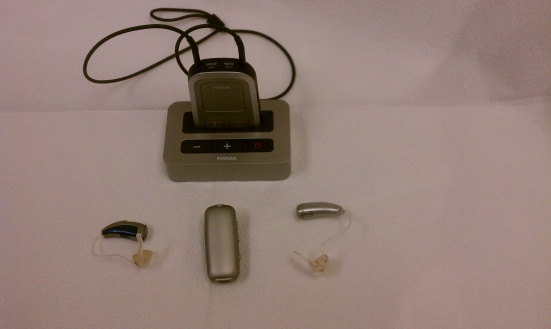 """This is my electronic hearing collection,"" writes Dave. ""Two hearing aids (the left aid transmits from deaf ear over to my right Aid), one remote Mic, one TV Bluetooth, and one around my neck program with volume and Bluetooth."""