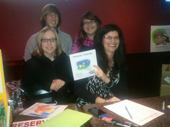 Allison Schley (right, seated) and friends with a copy of Forever Friends